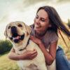 Woman on a green grass with dog Labrador retriever.